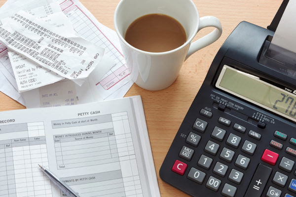 Bookkeeping sales ledger, invoices and a print calculator