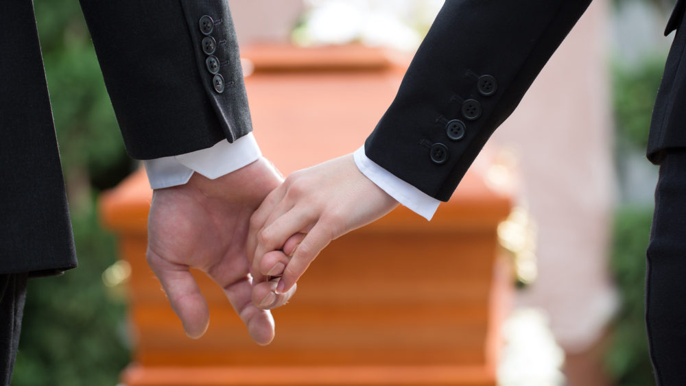 A parent gently holding hand of youth in suit in front of casket
