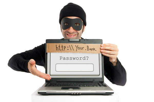 Masked scammer holding a computer inviting you to give him bank information