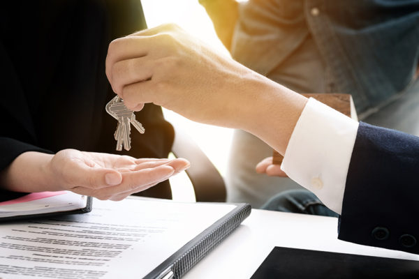 rental agent giving keys to man and sign rental agreement in office for a business