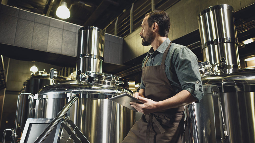 Brewery Owner in apron inspecting industrial equipment at the brewery