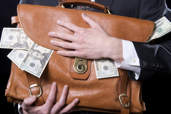 Closeup of man holding briefcase with money spilling out close to his chest