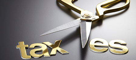 A pair of gold scissors cuts through the word taxes – Bruton, Nissen and Schellberg can help you with your Taxes, Accounting and Bookkeeping in Bellingham, WA.