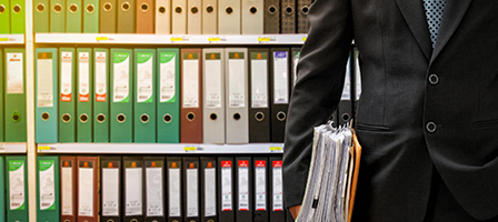 man holding a bunch of papers, standing in front of a bookshef full of binders. Bruton, Nissen and Schellberg Taxes, Bookkeeping and Accounting firm located in Bellingham, WA.