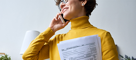 Professional woman on a phone holding papers.. Bruton, Nissen and Schellberg Taxes, Bookkeeping and Accounting firm located in Bellingham, WA.
